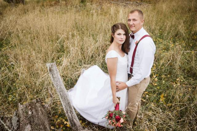 Bride and groom embrace in a straw field