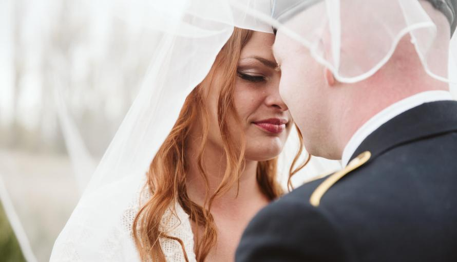 Bride and groom stand together under veil with eyes closed.