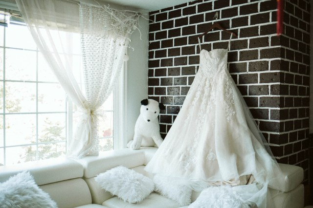 Wedding dress hangs on a brick wall in a house over a white couch