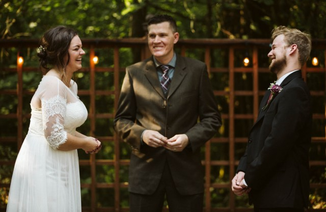 Bride and groom stand in front of the wedding officiant while laughing.