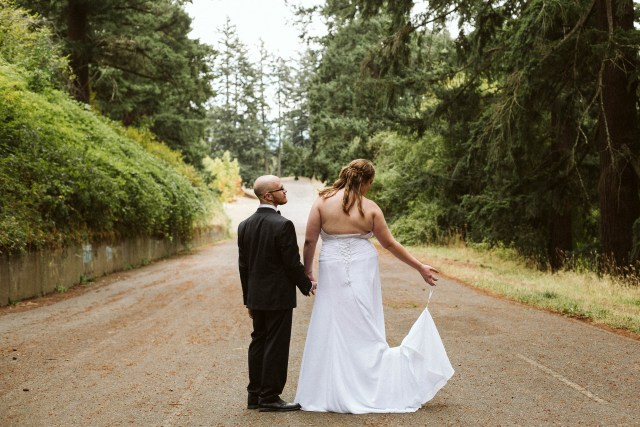 Portland groom looks at bride while she looks at dress