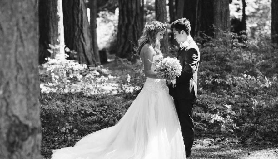 Groom and bride stand facing each other while touching foreheads in the forest.