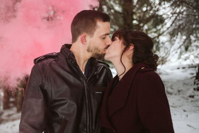 Man and woman kiss in front of light red smoke bomb