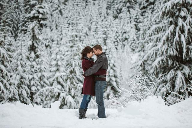 Man and woman stand in snow in front of snowy trees holding each other.