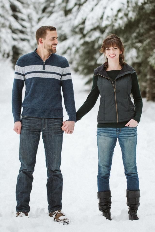 Man looks and smiling wife while standing side by side in snowy Washington forest