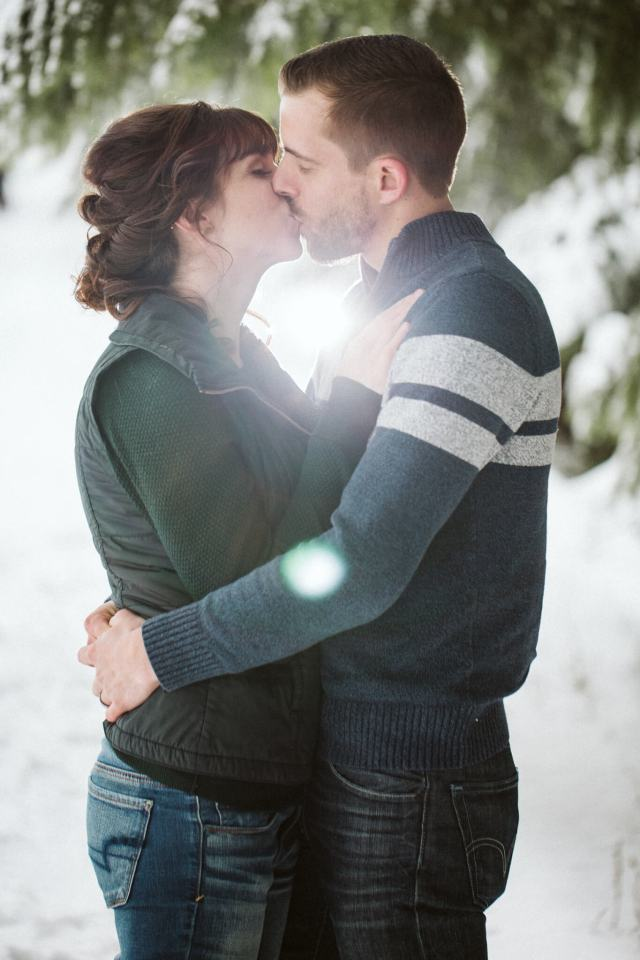 Husband and wife kiss together in front of flash of light in snowy Washington forest