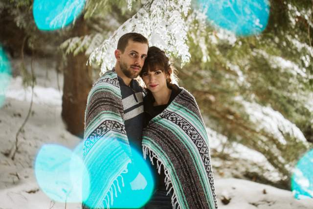 Husband and wife stand together wrapped in blanket in snowy Washington forest with teal bokeh