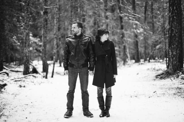 Husband and wife stand side by side looking away from each other in snowy Washington forest.