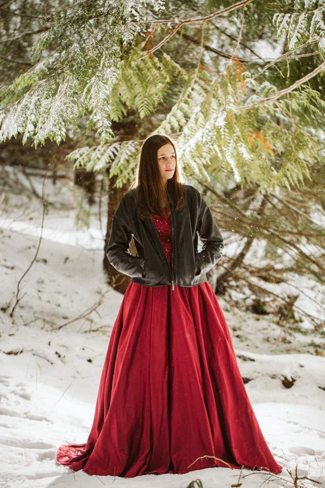 Teen girl stands under snowy tree with red prom dress and black leather jacket