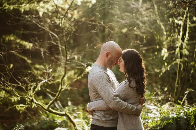 Man and woman stand in a hug with the back light of the sun through the Pacific Northwest forest.