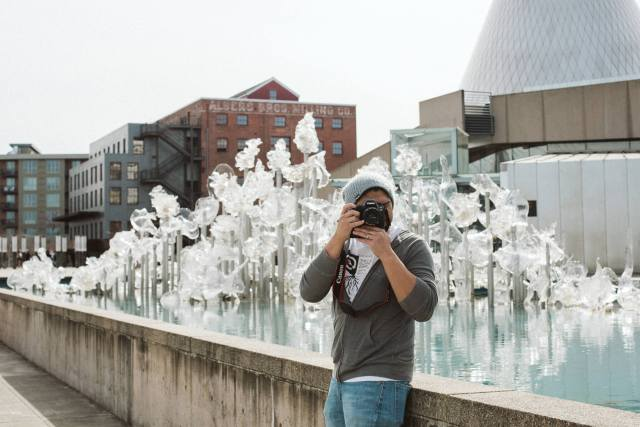 Man stands taking a picture in front of the Tacoma Museum of Glass