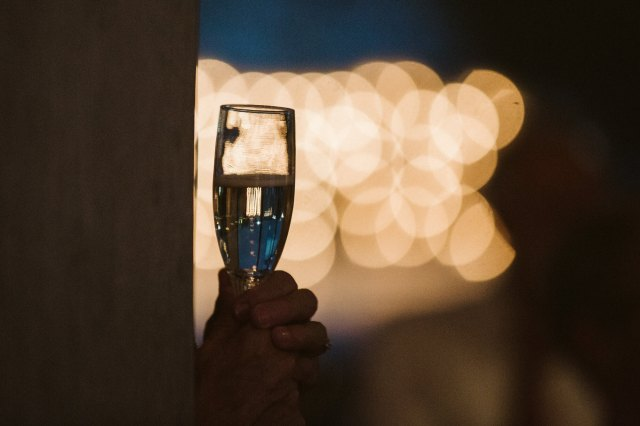 A full champagne glass is held in front of bokeh christmas lights