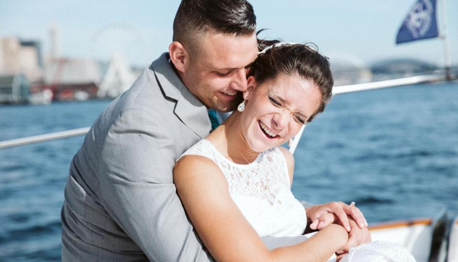 Seattle Bride and groom sit in the front of a boat together on the Puget Sound outside of Seattle