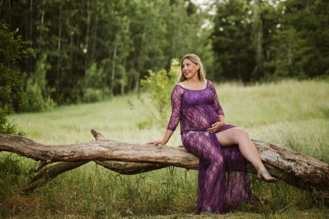 Pregnant woman sits on long, low tree branch wearing purple lace dress