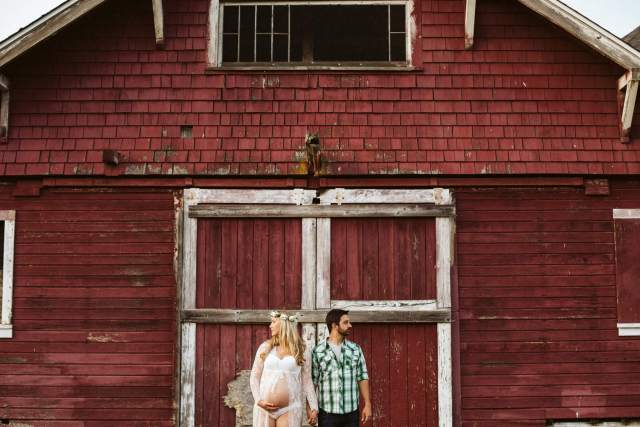 Pregnant woman and husband stand side by side in front of barn.