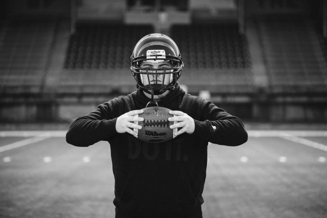 black and white of senior boy with football helmet on holding football at chest height in front of empty stadium.