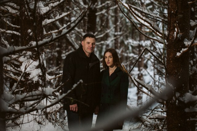 Man and fiancee stand in the middle of a snowy forest and look at the camera seriously