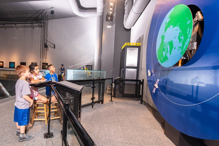 Three children stand in front of an aerospace exhibit demonstrating how space shuttles dock with the ISS.