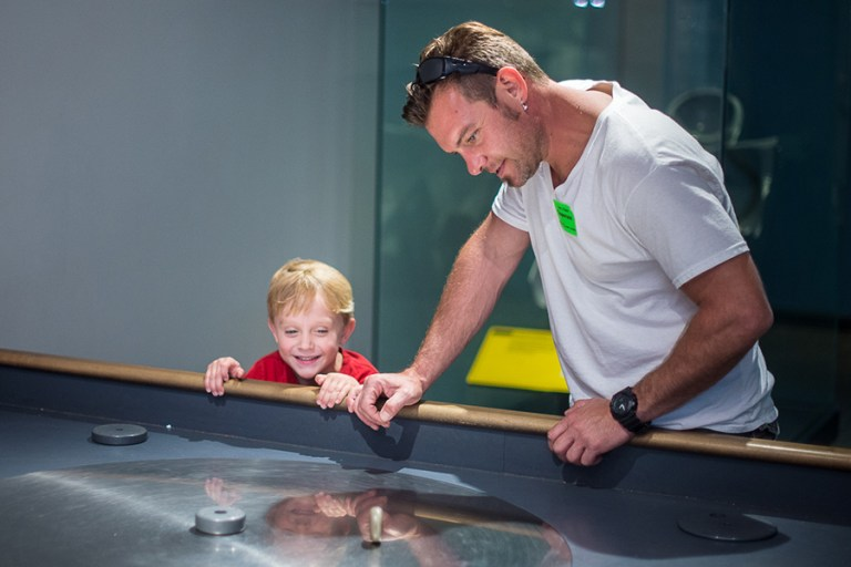 Adult and child in Aerospace gallery using the turntable.