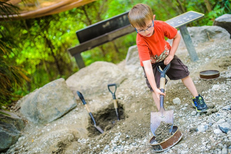 A young boy scoops a shovelfull of dirt into a sifter.