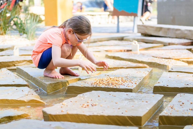 Girl plays with rocks in stream of Earth Moves