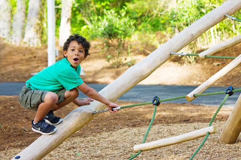 A boy in a green shirt climbs up the side of a rope climber.