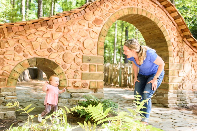 A mom and small child play peek a boo around a wooden arch.
