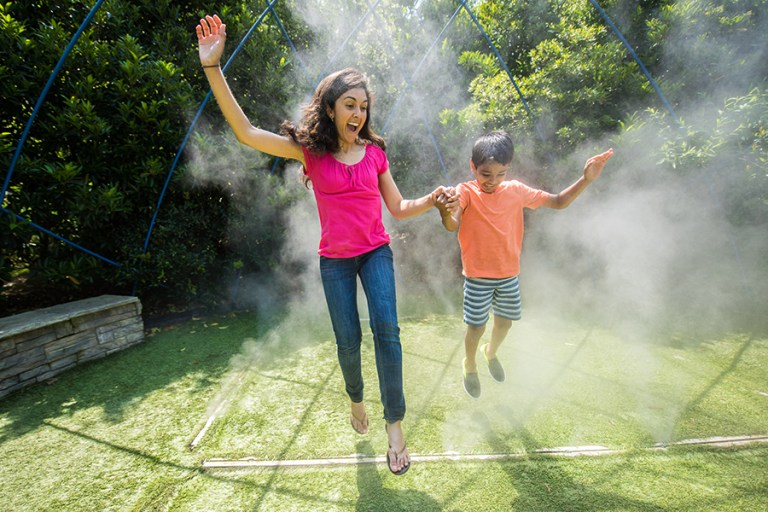 A woman and boy jump through a cloud of mist under a blue wire dome.