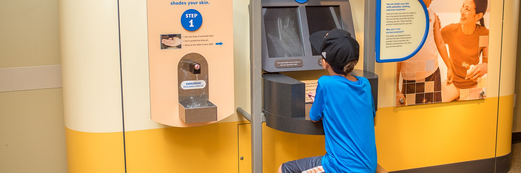 A boy sits at the sunscreen station and looks at his hands under UV light.