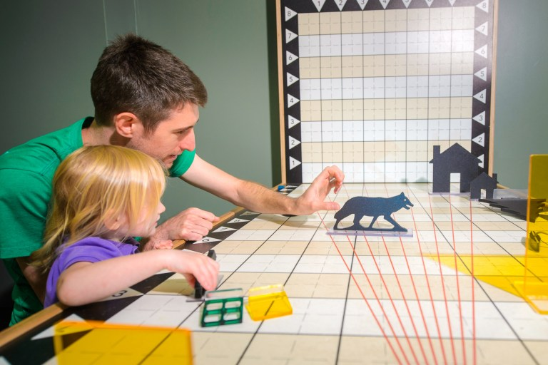 A man moves a wolf figure on a table with gridlines as a girl watches.
