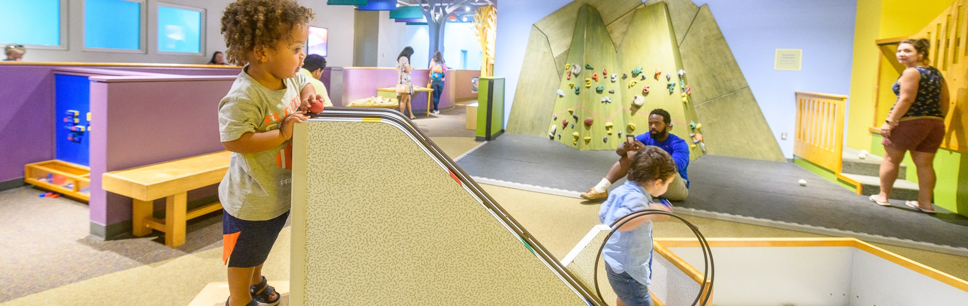 A child plays with a ball ramp in a brightly lit room as an adult watches.