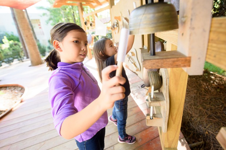 A girl in a purple shirt plays bells with a mallet.