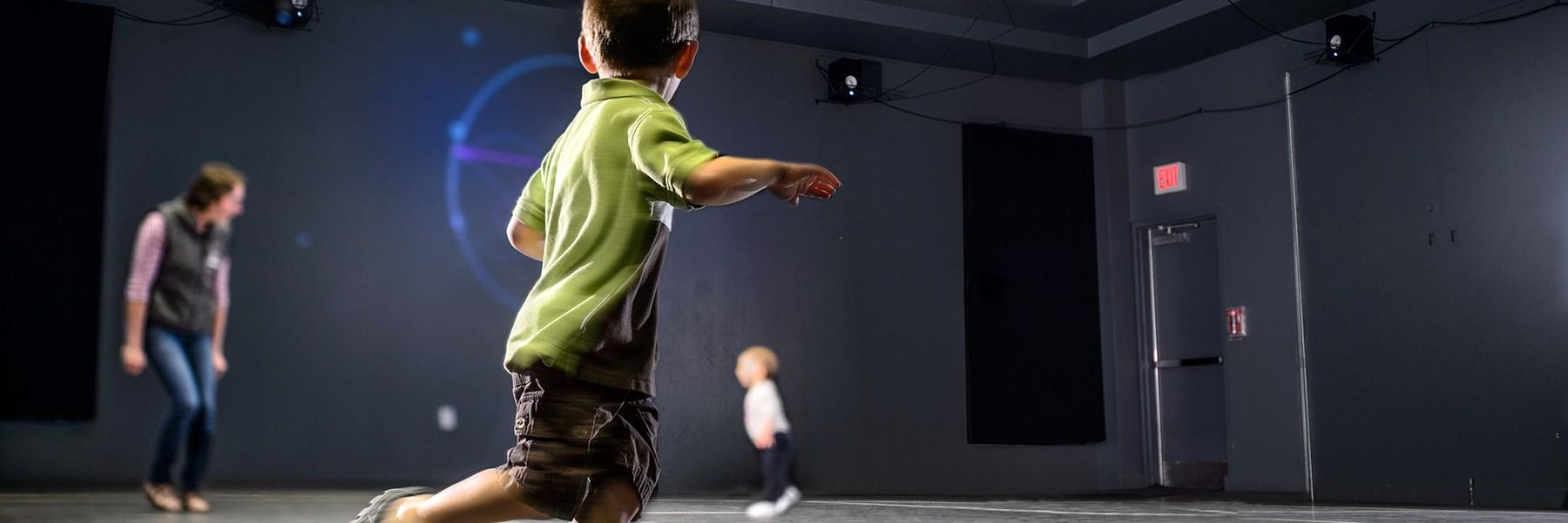 A boy runs through a room that plays sounds.