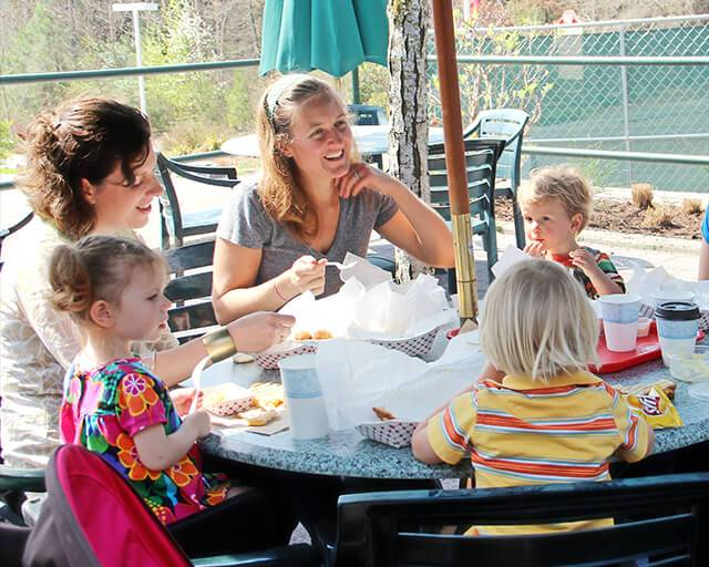 Adults sitting at outdoor dining table with chidren, eating a meal