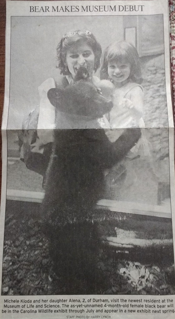 Newspaper clipping of visitors look at young bear
