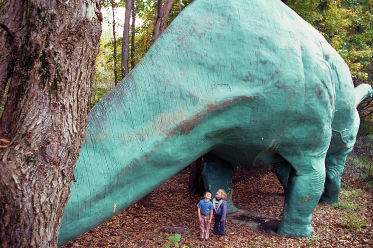 Two children stand under a large brontosaurus sculpture.