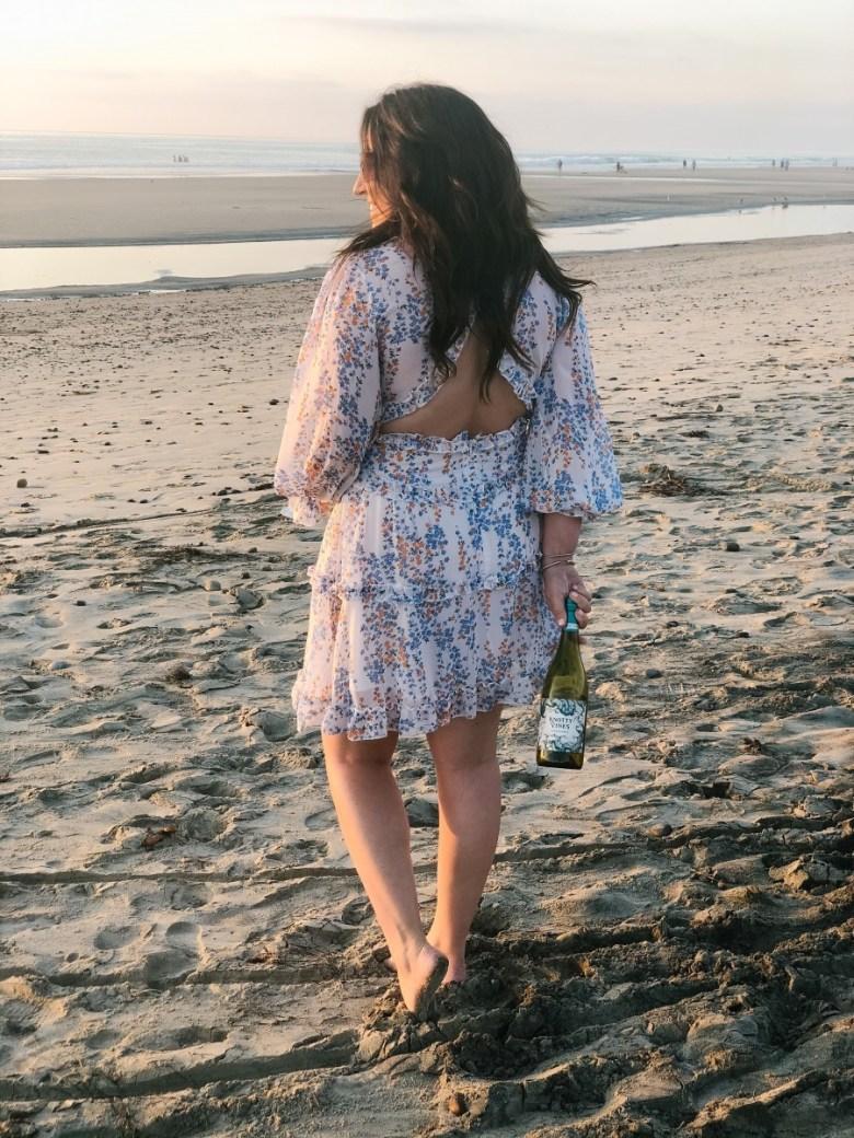 girl on beach drinking wine