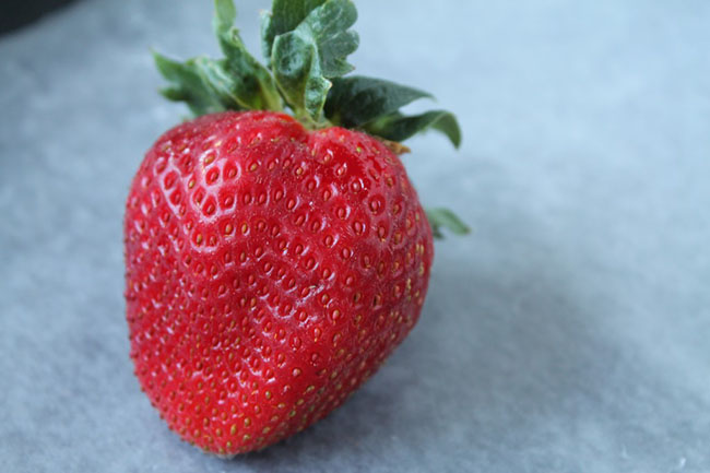 Fresh strawberry sitting on a piece of waxed paper