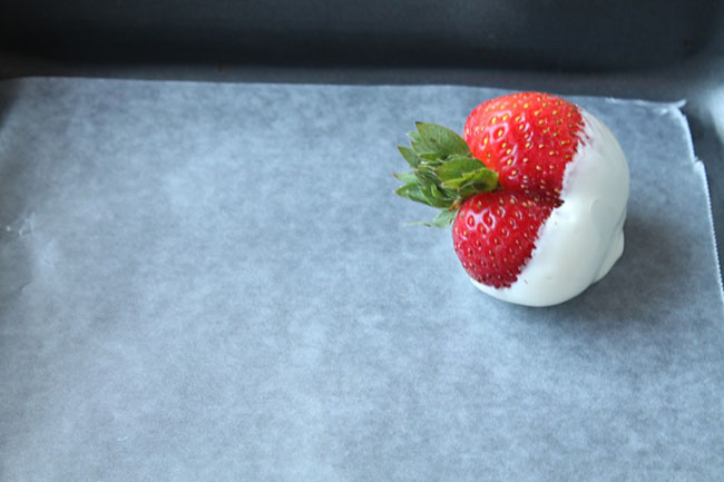 fresh strawberry dipped in white chocolate sitting on a baking sheet