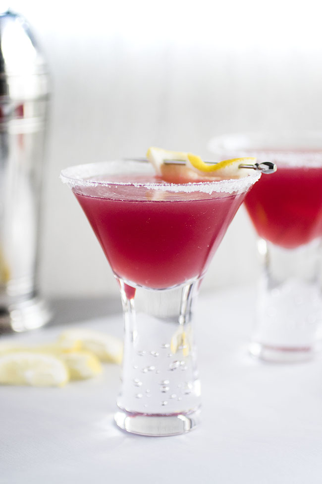 Jolly Pop cocktail in a tall martini glass with a lemon wedge garnish.
