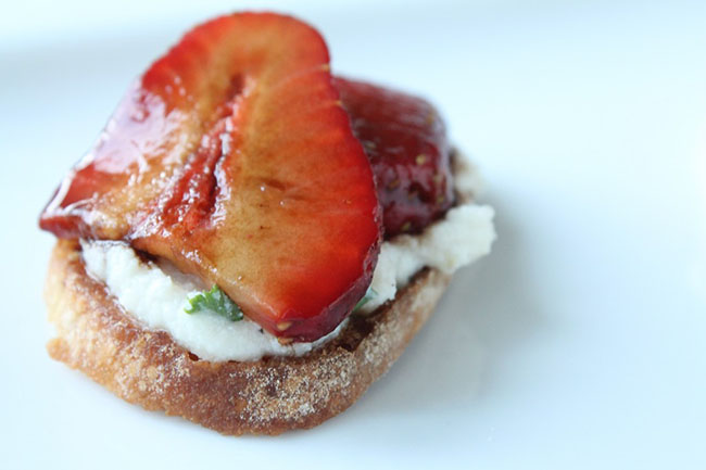 Crostini topped with cheese and fresh strawberries on a white plate