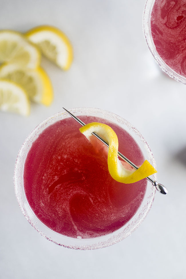 Pink Jolly Pop cocktail in a martini glass, garnished with a lemon twist.