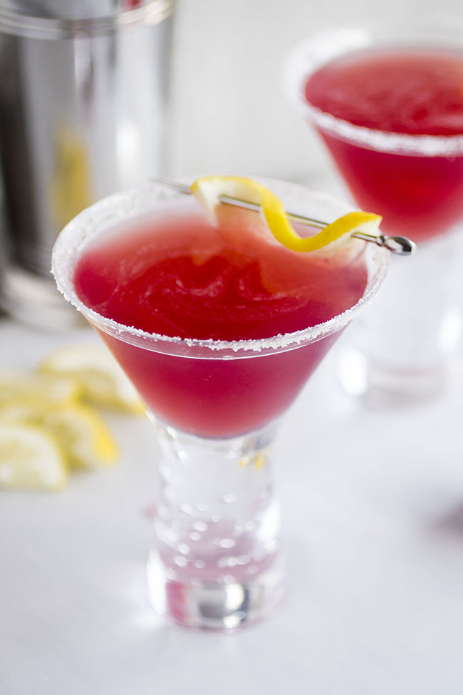 A bright pink Jolly Pop cocktail in a martini glass with a lemon wedge garnish.