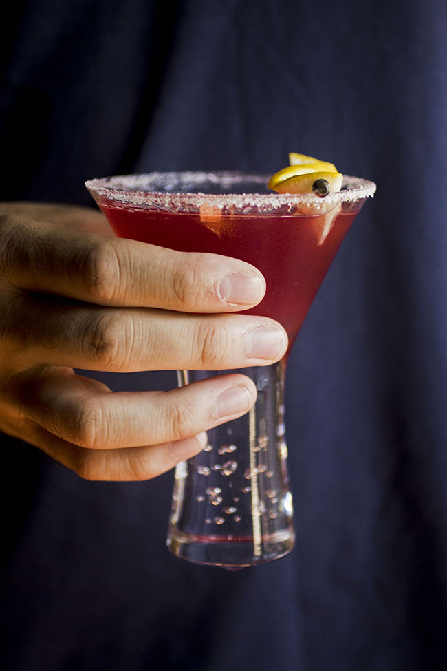 Man\'s hand holding a Jolly Pop cocktail in a martini glass.