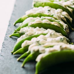 Snap peas stuffed with cheese arranged on a slate serving platter.