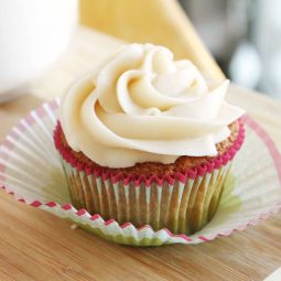 Vanilla cupcake with white frosting on a wooden cutting board.
