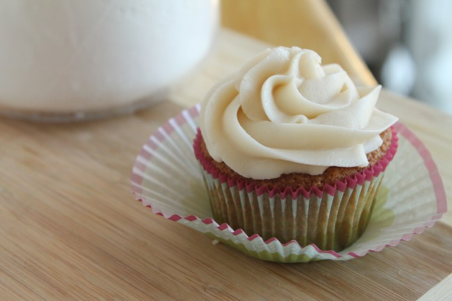 Vanilla cupcake with white frosting on a wooden cutting board next to a jar of powdered sugar.