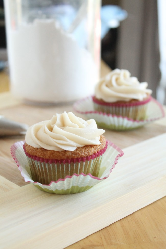 Two vanilla cupcakes with white frosting on a wooden cutting board next to a pastry bag.
