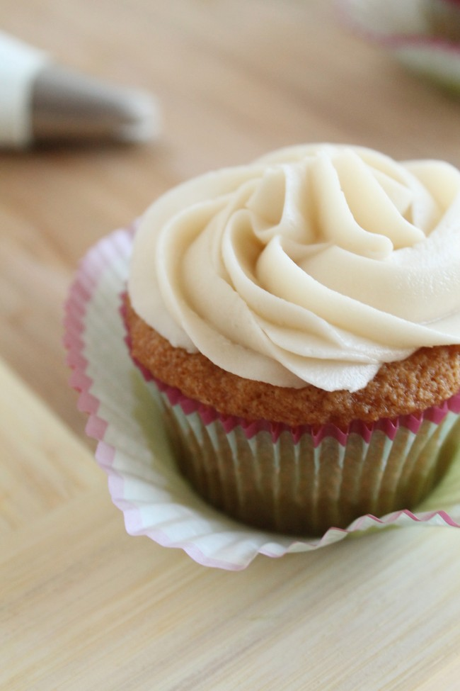 Vanilla cupcake with white frosting sitting in a peeled-off cupcake liner.