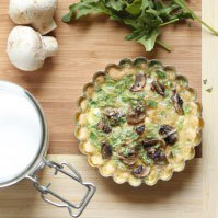 Mushroom quiche in a small tart pan, sitting on a wooden surface.